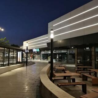מתחם הקניות והבילוי - גן שמואל. שלושה פסי תאורת לד מעטרים את קצה המבנה. תאורה עמודים רכה