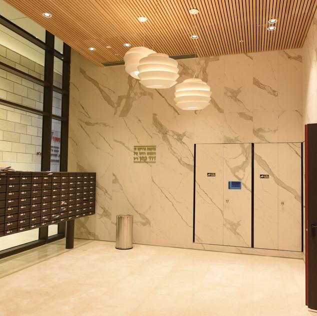 לובי הכניסה לבנין, שילוב בין גופי תאורה גדולים התלויים מהתקרה, לצד גופי תאורה שקועי-תקרה