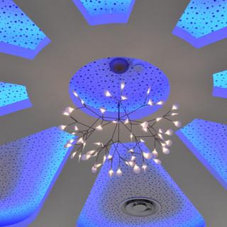 שנדליר מודרני תלוי במרכזו של אלמנט עיצובי בתקרה. סביב תאורה נסתרת בגוון כחול עדין