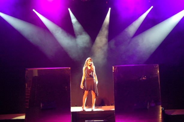 שחקנית במרכז הבמה. 6 אלומות אור מכוונות למרכז, בעומק אור סגול