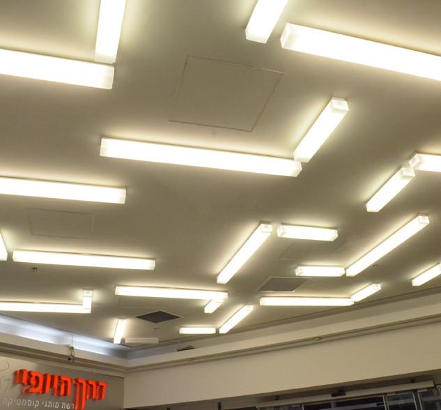 זיגזג של אור. גופי תאורה מאורכים יוצרים תבנית ייחודית על התקרה