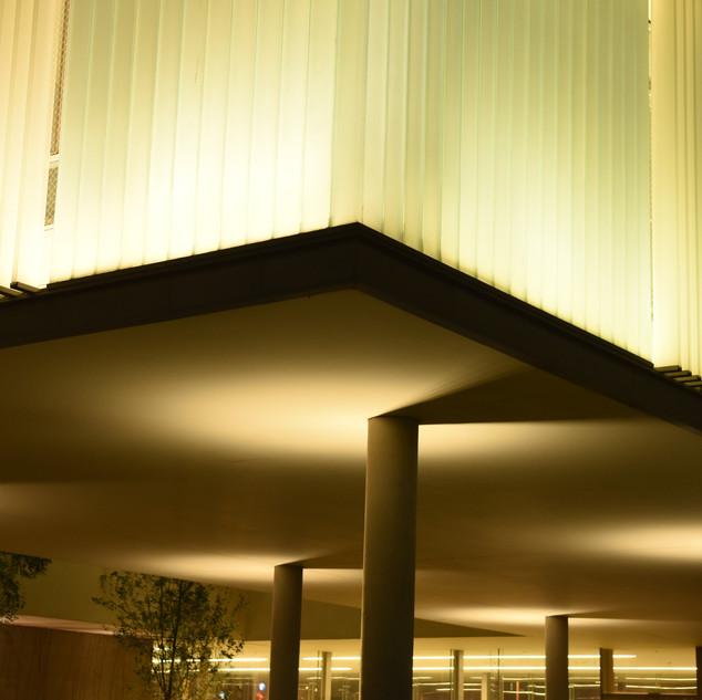 עמודי התמיכה של הבניין מוארים, ויוצרים פאטרן על התקרה
