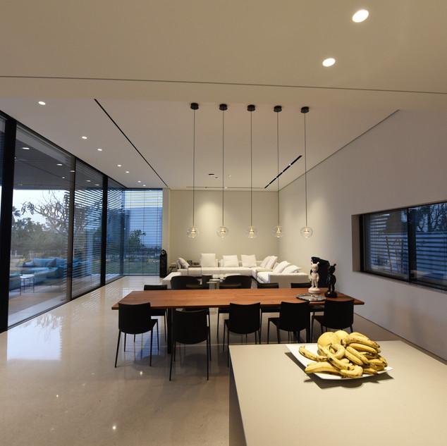פינת האוכל - מבט מן המטבח. חמישה גופי תאורה מעל לשולחן האוכל