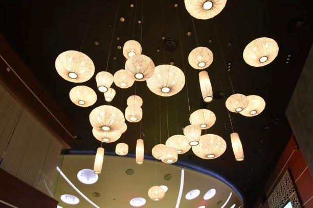 גופי תאורה עגולים בגדלים שונים תלויים מהתקרה