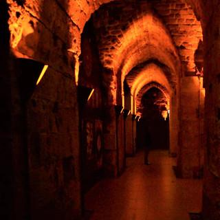 מסדרון ארוך, מואר בתאורה בלתי ישירה, דמויית לפידים, המאירים את התקרה העתיקה.