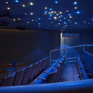 אודיטוריום הצפייה של מרכז המבקרים, השמיים זרועי כוכבים. גופי תאורה מפוזרים רנדומלית בתקרה, בצבעוניות של כחלכל וצהבהב.