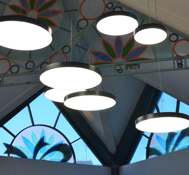 גופי תאורה עגולים ושטוחים -  בגדלים שונים תלוים מהתקרה ויוצרים אפקט מודרני ומרשים