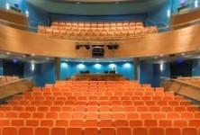 מבט מכיוון הבמה אל האולם, כיסאות אדומים, קירות כחלחלים, מוארים בתאורה רכה