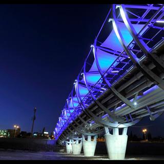 פיסות-הבד שנועדו להצללה נצבעות בערב בצבעי התאורה הכחלחלה. עמודי הבטון של הגשר מוארים באור לבן.