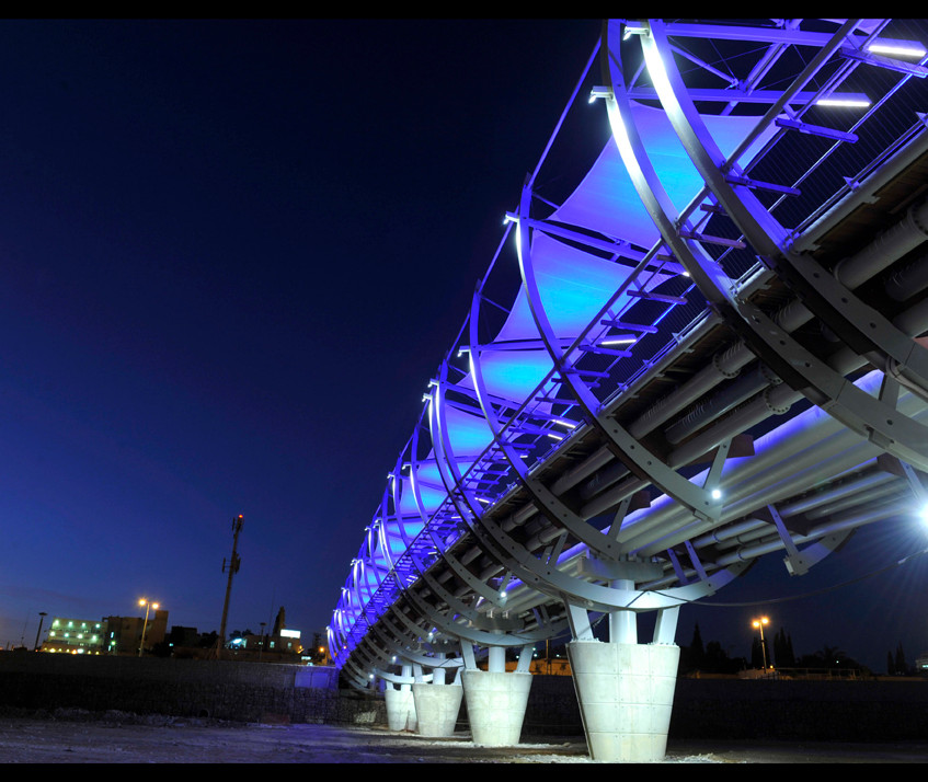 The bridge from below. The pillars and sheds are illuminated in blue