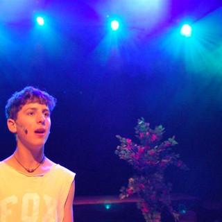 שחקן בקדמת הבמה, מאחוריו 5 פנסים באור כחול רך מפזרים אלומות צרות