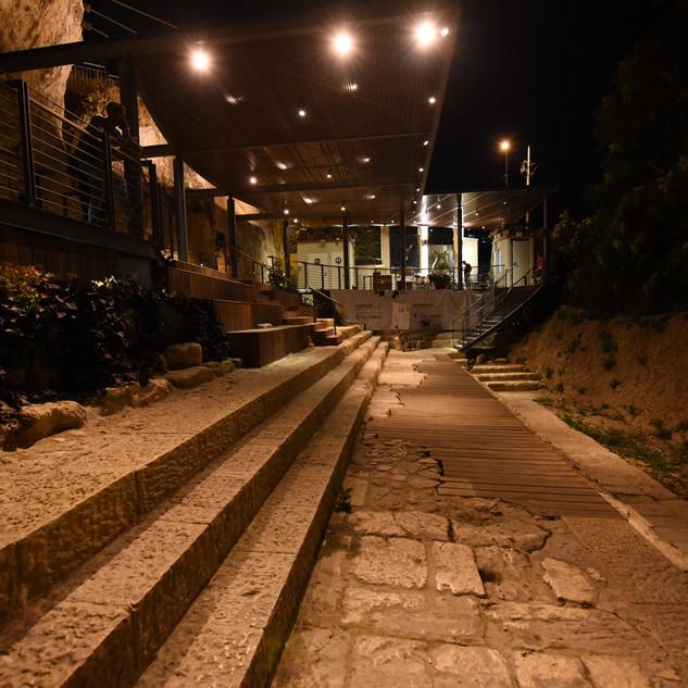 מדרגות השילוח מוארות ומעל בסככה תאורה עם גופי תאורה קטנים וממוקדים