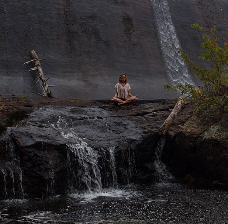 Yoga teacher Gina Mandella meditating at a waterfall