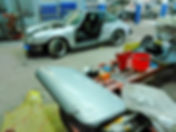 Customer's silver Porsche Targa wrongly parked in body shop work area with driver-side door, front hood and front bumper removed from car... car's door by itself lays on table in foreground with side mirror and door handle removed
