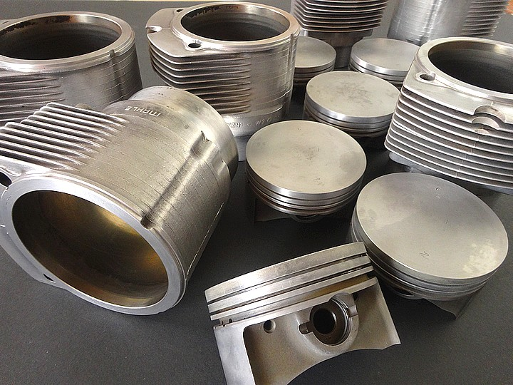Porsche pistons and cylinders are laid on table