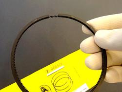 New Porsche piston ring held in hand