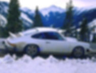 Profile of 1974 white Porsche Carrera parked on sloping Rocky Mountain road shows car's lowered ride height relative to optimal high speed handling
