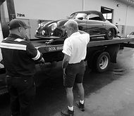 george perdomo speaking with tow truck driver delivering porsche 356 to shop