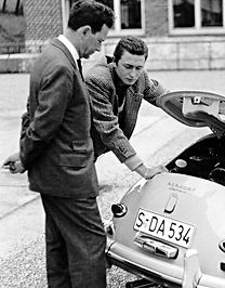 Ferry Porsche with his eldest son Butzi Porsche with both of them looking into engine area of a 356 A circa 1958