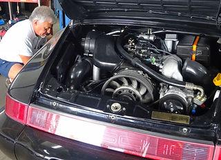 Peorge Perdomo kneeling next to black Porsche while performing Porsche PPI