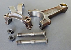 Clean Porsche connecting rod assembly laid out in pieces includng rod top, bottom cap, two nuts and rod bolts, and bearings