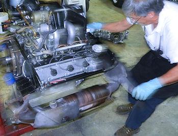 George Perdomo pulling Porsche engine on its stand inside his miami porsche shop