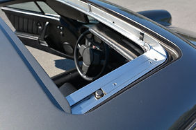 Porsche 911 sunroof is open showing polished chrome trim