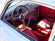1954 Porsche 356 interior with wood steering wheel and red seating