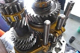 porsche transmission gears, syncros, and dog teeth being inspected in miami porsche shop of gp autowerks