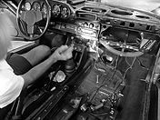 george perdomo sitting in the seat of a porsche that he is repairing