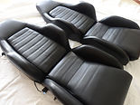 Pair of Porsche sport seats laid flat with new black leather covers completely installedwith