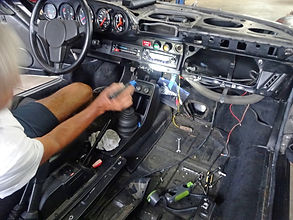 Posche interior being serviced by George Perdomo with him making repair to dashboard