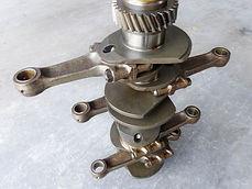 Clean Porsche crankshaft standing on end with connecting rods attached in miami porsche shop of gp autowerks