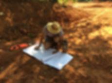 man in hat, cat beside drawings