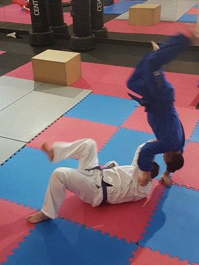 A stomach throw being performed by a person in a white gi on a person in a blue gi