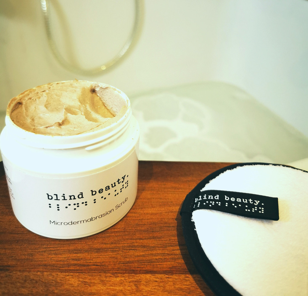 Blind beauty microdermabrasion scrub and cleansing sponge sitting on a wood board with the bath running in the background