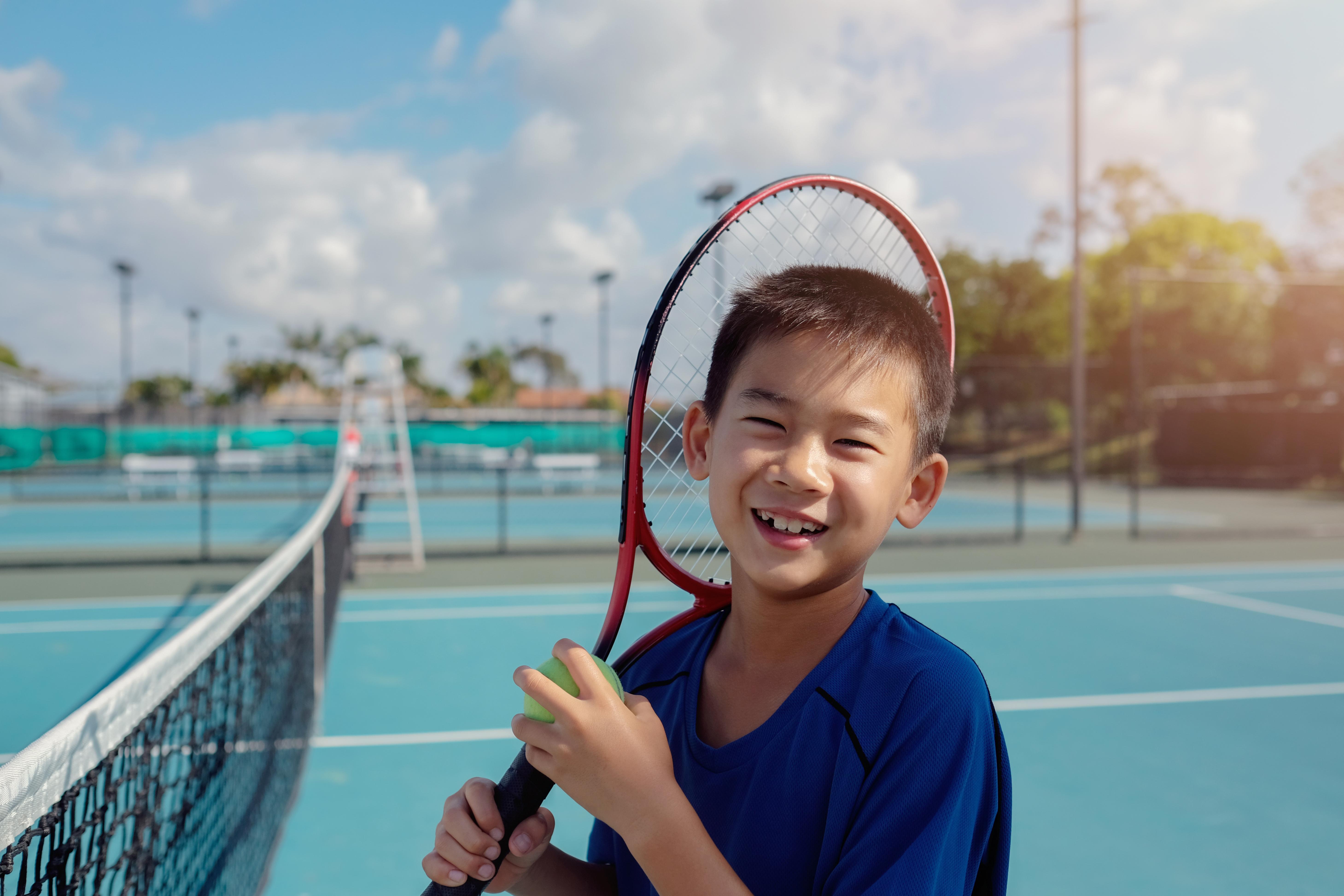 Young tween Asian boy tennis beginner pl