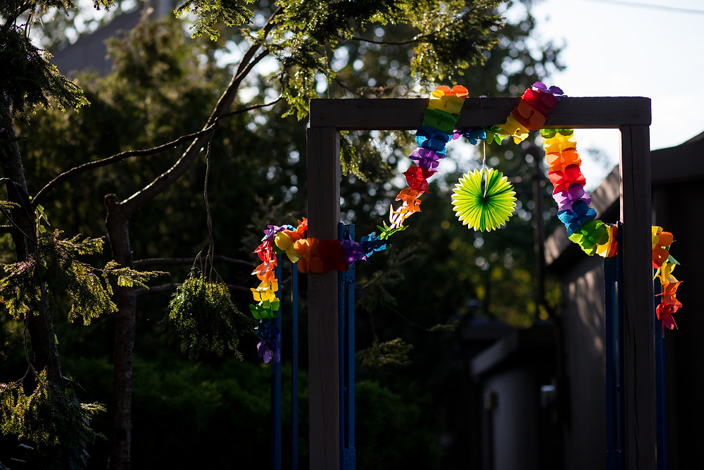 Paper rainbow decorations on an outdoor gate.