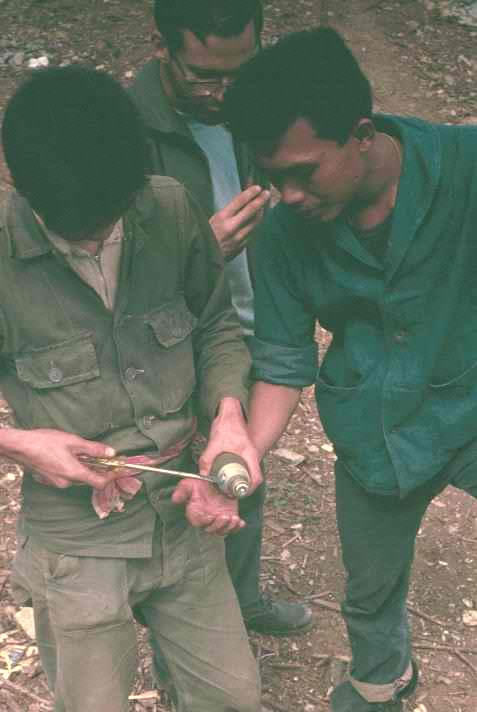 Thai disarming a mortar round so Dick Grimes can take it home as a souvenir