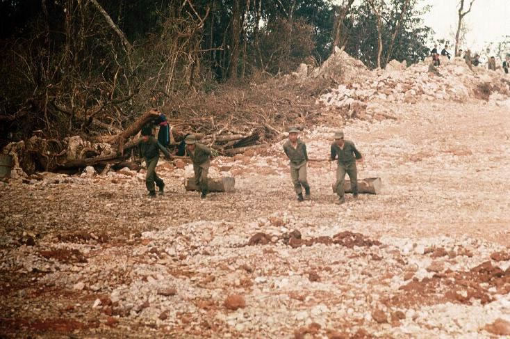 Hmong clearing the LZ. Note the half 55 gallon drums as rock sleds