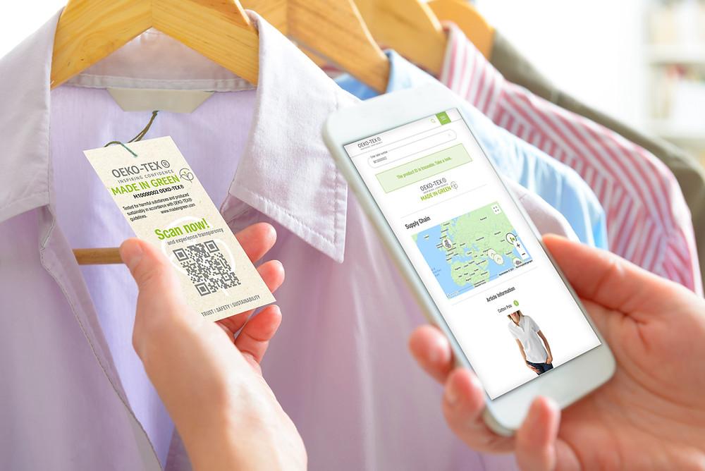 Eine Hand hält das Hangtag von Made in Green, die andere Hand scannt mit Handy den QR-Code.