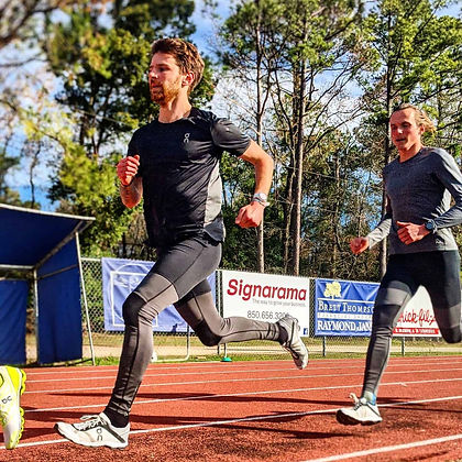 Two men in long tights and t-shirt running on red track