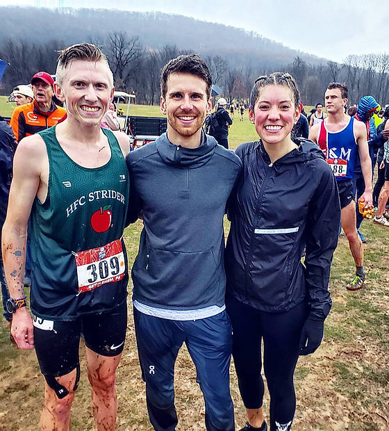 Male and female runner with coach after race