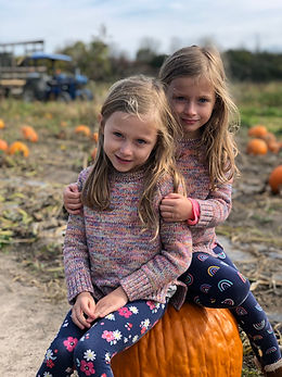 adorable girls in pumpkins.jpeg