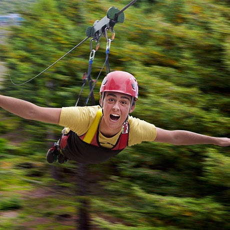 person ziplining in superman harness