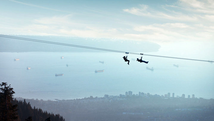 two people going down a towering zipline