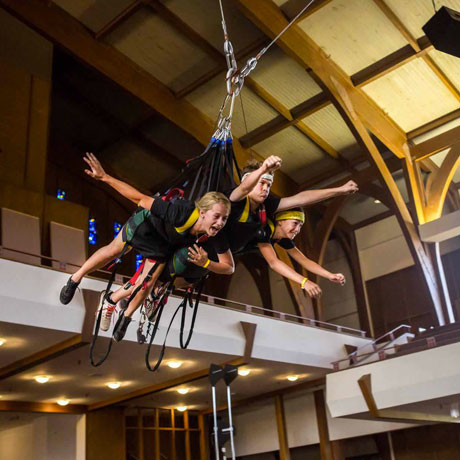 three kids in superman zipline harness
