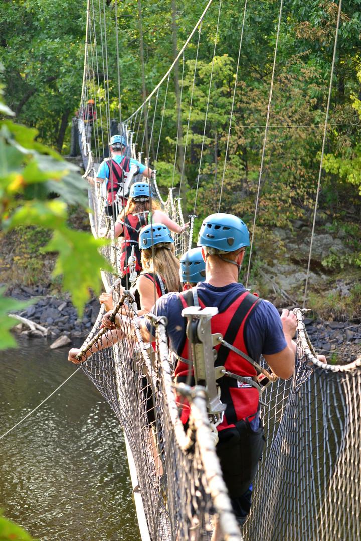 people walking across suspension bridge