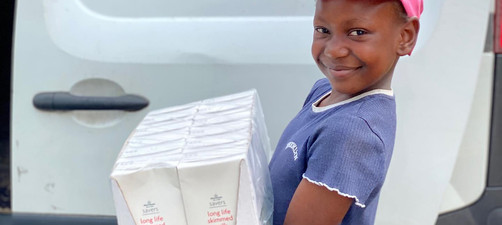 Our youngest Volunteer, Alexi carrying desperately need milk donation