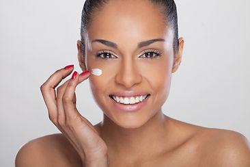 Model applying cream to remove eye bags